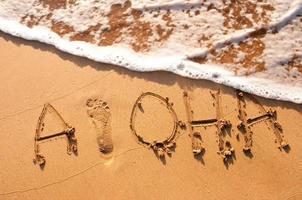 aloha skriven i sanden foto