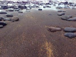 svart sandstrand foto