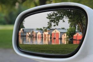 reflektion i sidospegeln av bilen, av båthus återspeglas i vatten foto