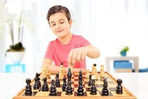 liten pojke som spelar schack som sitter på ett bord foto