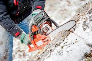 träsnitt eller skogsarbetare som skär eld ved i trädgården under vintern foto