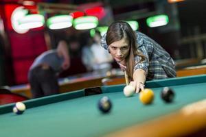 ung kvinna som spelar pool foto