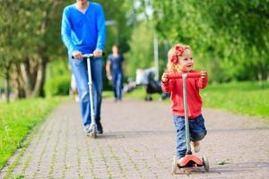 far och lilla dotter som rider på skotrar foto