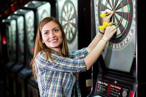ung vacker kvinna som spelar dart i en klubb foto