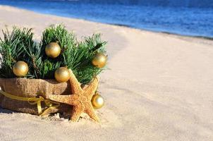 julgran med gyllene julgranskulor, sjöstjärna på sand, strand foto