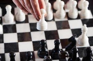hand med vit bonde över schackbrädet foto