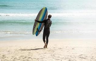 ung surfare på stranden foto