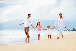 lycklig ung familj som går på stranden