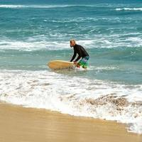 surfar vid havet står med en surfbräda foto