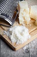 riven parmesanost och rivjärn av metall foto