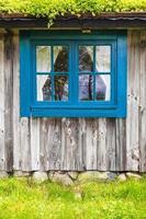 forntida svenskt trägård med blått fönster