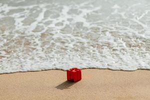 present röd låda på stranden foto