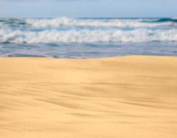 sandstrand med vågor i fjärran