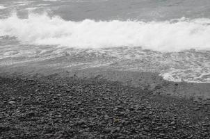 svart sandstrand vid waianapanapa delstatspark i maui, hawaii