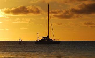 solnedgång med katamaran och paddel-boarder foto