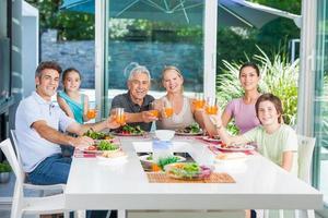 familj med flera generationer som äter utomhus foto