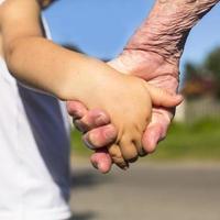 närbildhänder, mormor som håller en barnhand foto