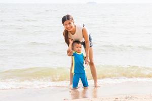 mamma och son kyla på stranden foto