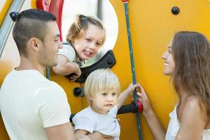 lycklig familj med barn på lekplatsen foto
