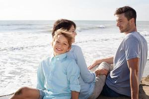 lycklig familj sitter vid stranden
