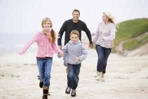 familj springer på stranden håller händer foto