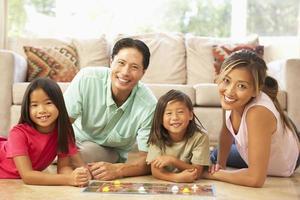 familj som spelar brädspel hemma foto