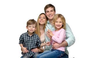 leende ung familj på fyra poserar