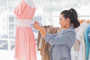 vacker modedesigner som mäter klänningen på en skyltdocka foto