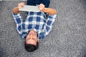 man ligger på golvet med surfplatta