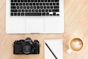 Ovanifrån arbetsyta med datorkamera och kaffe foto