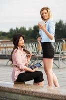 två unga kvinnor som innehar en digital tablet-datorer foto