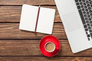 kopp kaffe och anteckningsbok med bärbar dator foto