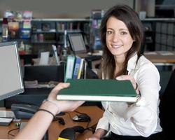 ung dam framför en dator som tar emot en bok foto