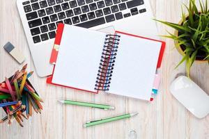 skrivbord bord med dator, leveranser och blomma foto