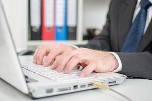 affärsman att skriva på en vit bärbar datortangentbord foto