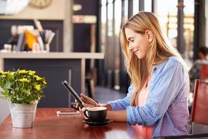 ung kvinna som använder dator på ett kafé foto
