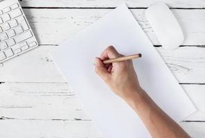 hand med penna och vit sida på träbakgrunden foto