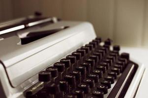 mekanisk skrivmaskin med svarta nycklar och vitt fodral foto