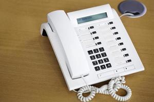 vit telefon på trä skrivbord foto