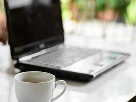 kaffekopp och bärbar dator för företag, selektiv inriktning på kaffe. foto