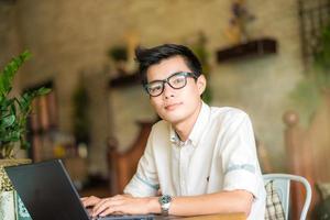 ung asiatisk student man använder surfplatta på café foto