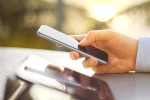 affärsman händer att skriva på en mobiltelefon foto