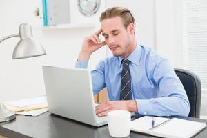 affärsman som sover vid sitt skrivbord foto
