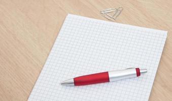 penna och papper på skrivbordet foto