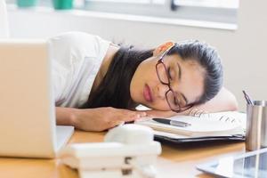 affärskvinna som sover på skrivbordet foto