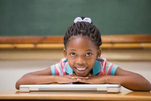 leende elev som sitter vid hennes skrivbord foto