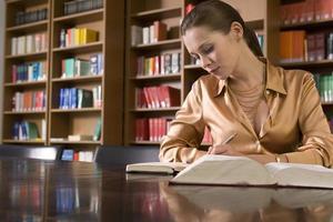 kvinna som studerar vid skrivbordet i biblioteket foto