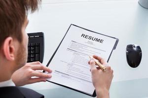 affärsman analysera CV vid kontorsskrivbord foto