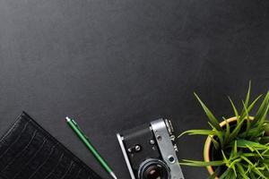 skrivbord med kamera, leveranser och blomma foto