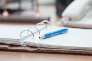 personlig arrangör och penna på skrivbordet foto